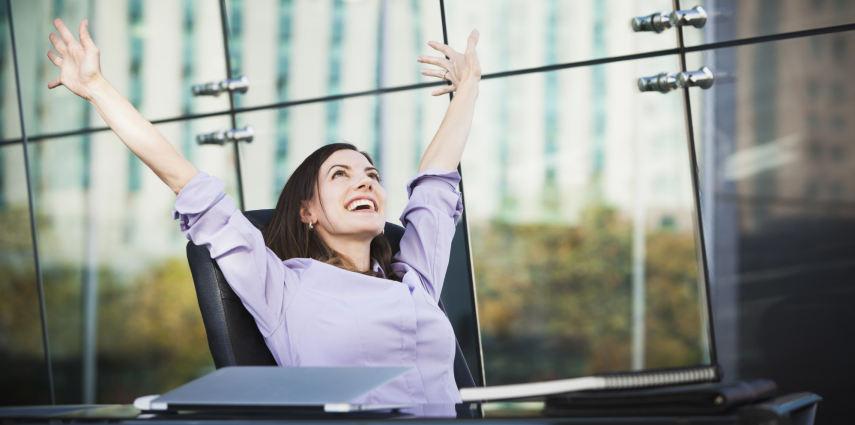 Caucasian businesswoman stretching at desk